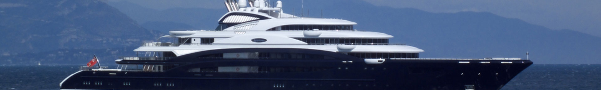 A superyacht with a dark blue hull at anchor