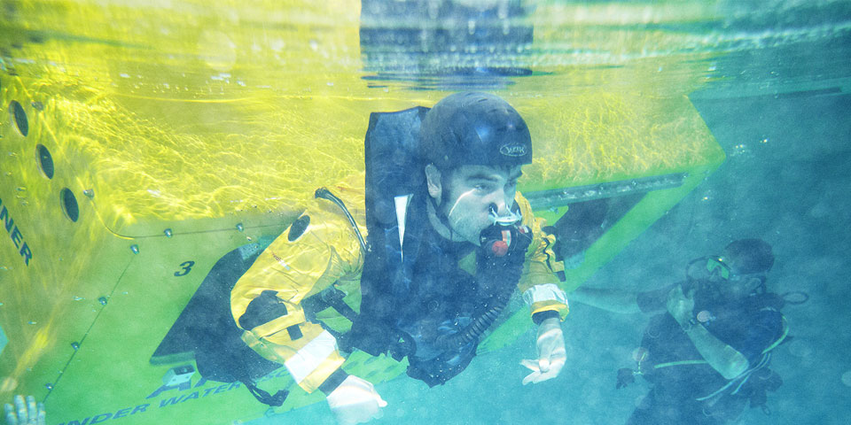 Underwater shot of a student emerging from the helicopter underwater escape trainer