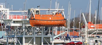 Lifeboat suspended at the end of the pier by the Hamble River