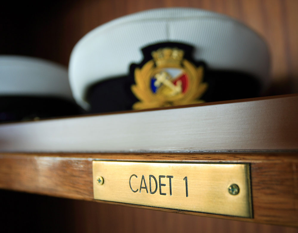 A Carnival cadet cap on a shelf with the label 'Cadet 1'