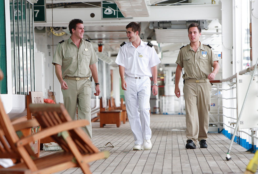 Carnival deck officers walking along the deck of a cruise ship