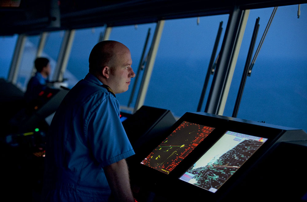 A deck officer on the bridge of a Maersk ship looking out to sea at night