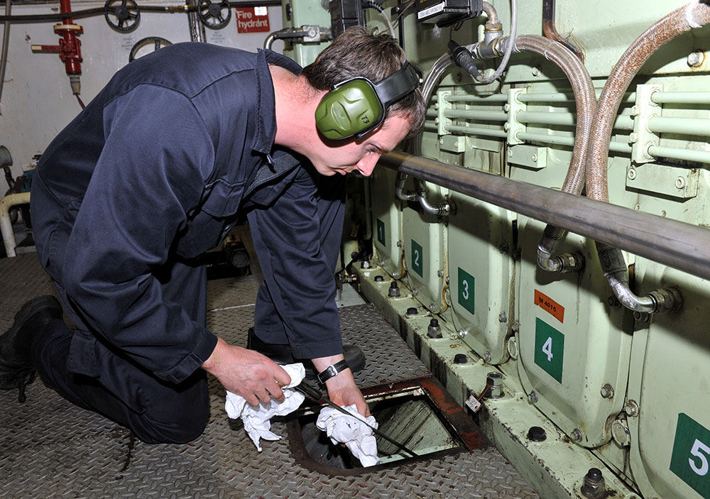 An engineer officer checking oil levels in a ship's engine room